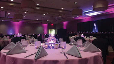 A circular table covered in a pink table cloth with gray napkins inside the banquet space at Hollywood Casino in St. Louis, Missouri.