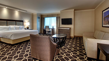 hotel suite with king bed, sitting chair, couch, tv