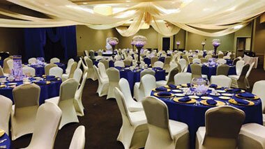 White material is draped from the ceiling over circular tables covered in dark blue table cloths and surrounded by chairs covered in white.
