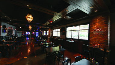 4-top tables at 99 Hops House with brick wall and chandelier