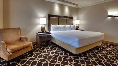 hotel room with king bed and sitting chair
