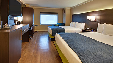 hotel room with two queen beds and tv