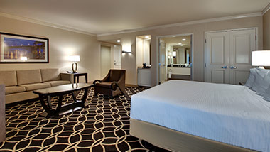 hotel suite with king bed, couch, sitting chair, master bathroom