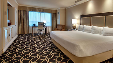 hotel room with king bed, office desk, tv