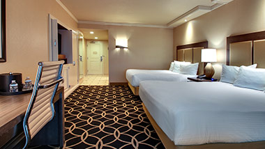 hotel room with tv, office desk, and two queen beds