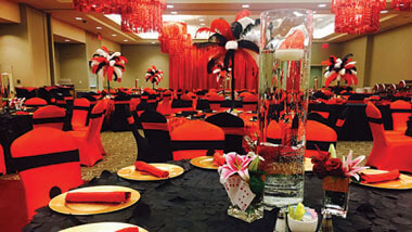 Red chandeliers hang over black tables surrounded by red and black decorated chairs inside the banquet space at Hollywood Casino in St. Louis, Missouri.