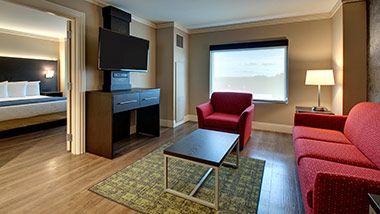 hotel suite with couch, sitting chair, tv, bedroom