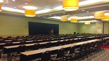 Conference room, many tables and chairs facing podium on stage