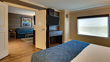 hotel suite with king bed, tv, living room