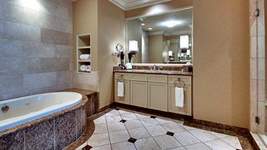 hotel bathroom with vanity and jacuzzi tub