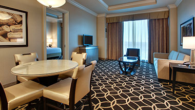 Hotel suite with tv, couch, dining table