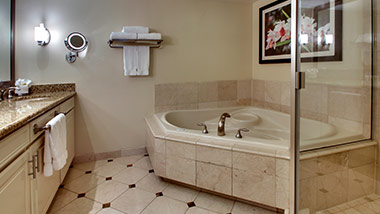 hotel bathroom with vanity, jacuzzi tub, shower