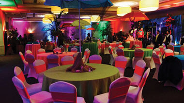 Chairs covered in bright material surround circular tables with green table cloths and palm tree center pieces at Hollywood Casino in St. Louis, Missouri.