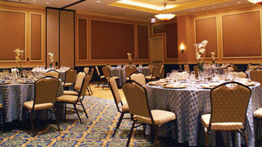 Wood-paneled banquet space filled with circular tables and chairs inside Hollywood Casino in St. Louis, Missouri.