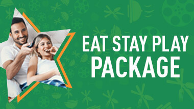 "Image of couple lying in bed inside a star cutout on top of a green background with the words ""Eat Stay Play Package."""