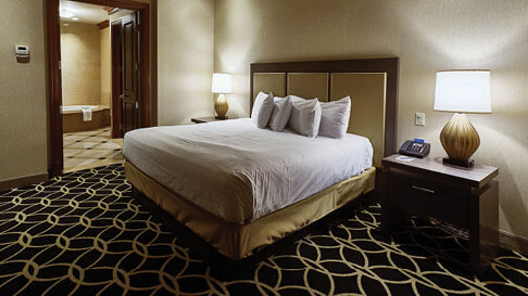 A king-size bed and two night tables inside a hotel room at Hollywood Casino in St. Louis, Missouri.