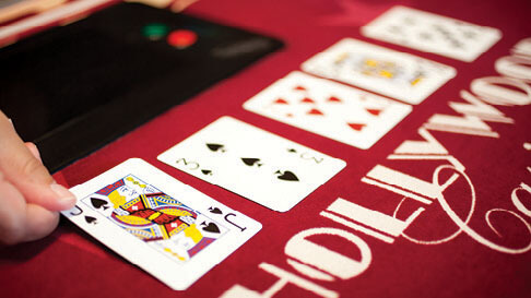 A dealer flips over a Joker card on a red felted poker table.