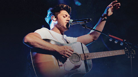 Musician Niall Horan sings in concert while holding a guitar.