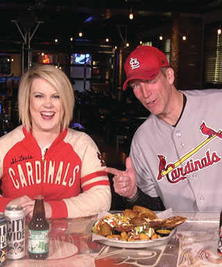 Man and woman laughing and wearing baseball clothing