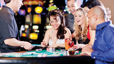People playing and laughing at a Baccarat table