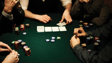 Hands, chips and cards on a poker table