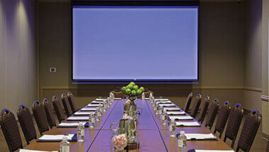 A boardroom table set up for a meeting with a large projection screen on the wall.