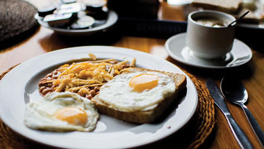 Sunnyside-up eggs on toast, a side of baked beans with shredded yellow cheese and a cup of coffee.