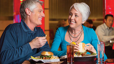 An older couple smiles as they eat burgers at Hollywood Casino in St. Louis, Missouri.