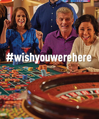 "group playing roulette with text ""#WishYouWereHere"""