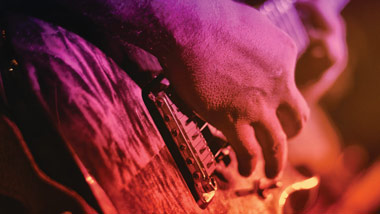 close up of hand playing guitar with pink, purple and gold overtones