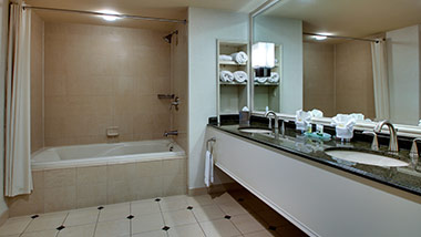 hotel bathroom with bathtub and double sink vanity