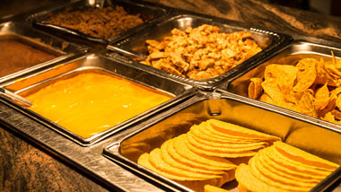 taco bar with shells, nachos, meat, cheese and beans