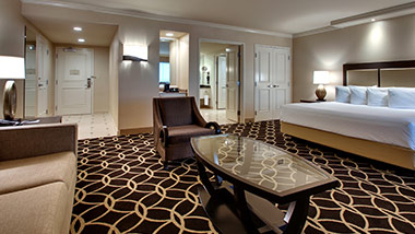 hotel suite with king bed, sitting chair, master bathroom