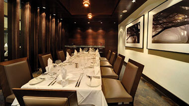 A long table set surrounded by tan and brown chairs and set with white linens inside Final Cut Steakhouse at Hollywood Casino in St. Louis, Missouri.
