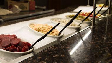 various vegetables and pasta salad items at salad bar