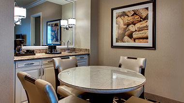 Hotel suite with dining table and wet bar
