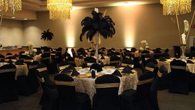 Chandeliers hang over tables covered in white lace with tall, feathered centerpieces inside Hollywood Casino St. Louis' banquet space.