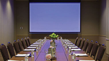 Chairs lined up on either side of a long board room table with a large projector screen on the wall.