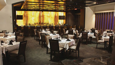 Four-top tables covered in white table cloths inside Final Cut Steakhouse at Hollywood Casino in St. Louis, Missouri.