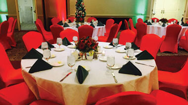 Chairs covered in red material surround a circular table set with a white table cloth and black napkins inside Hollywood Casino in St. Louis, Missouri.