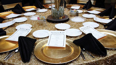 Menus lie on gold plates on a gold table cloth with black napkins inside the banquet space at Hollywood Casino in St. Louis, Missouri.
