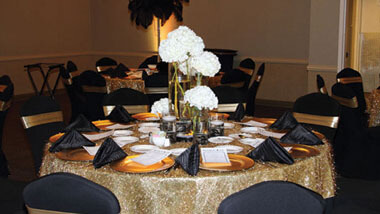 Blue chairs surround a circular table covered with a gold table cloth, gold plates and black napkins. A centerpiece contains white flowers.